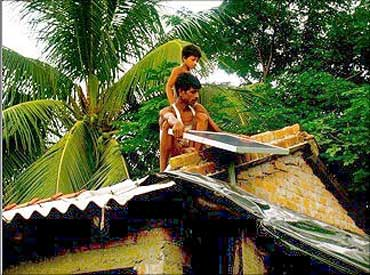 A villager installs a solar panel on the roof.