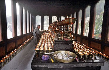 A Bhutanese man lights butter lamps inside a temple in Thimphu.