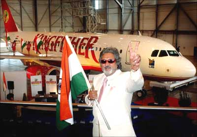 Vijay Mallya pose beside a Kingfisher aircraft.