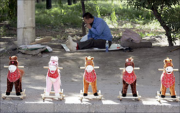 Toy horses are displayed for sale as a vendor smokes in the background on a street in Taiyuan.