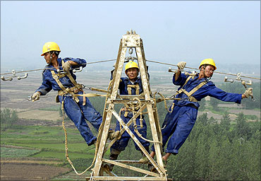 Labourers repair electricity cables on a power tower in Chuzhou.