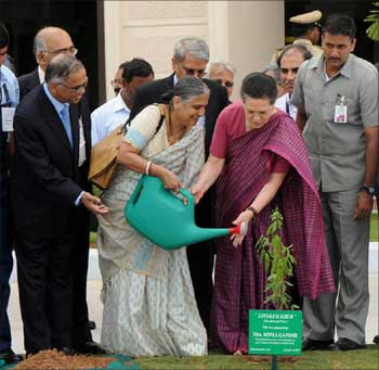 Sudha Murthy helps Sonia Gandhi to water a plant at the Infosys campus in Bengaluru.