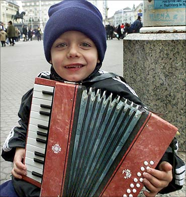 A five-year old Croatian boy plays an accordion to get some money for a Christmas gift.