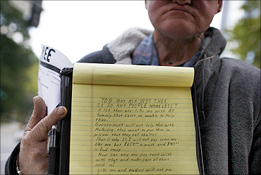 A homeless man who cannot speak, holds up a piece of paper explaining why many people are homeless.