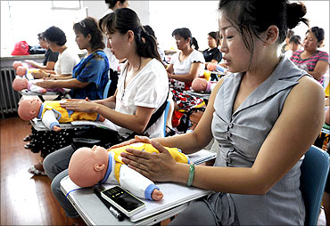 Chinese women learn baby sitting skills.