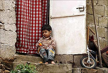 A boy sits on the front steps of his house in a slum in Algiers.