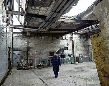 An idle worker walks through a damaged hall of the Sarabon chocolate factory in Sarajevo.