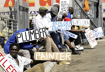 Men hold placards offering temporal employment in Glenvista, near Johannesburg.