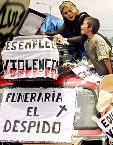 Two citizens of Medellin protest over an improvised coffin against the unemployment in Columbia.