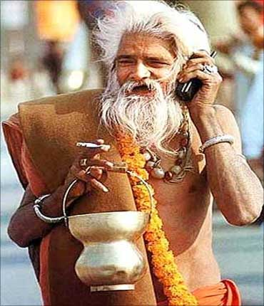 A sadhu speaks on his phone at Kumbh Mela.
