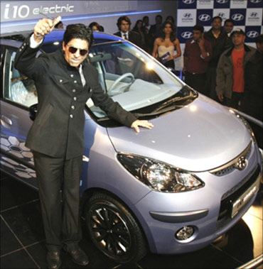 Shah Rukh Khan poses with Hyundai's i 10 electric car at India's Auto Expo in New Delhi.