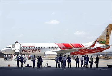 Journalists look at a new Boeing 737-800 aircraft in the livery of Air India Express at Mumbai airport.