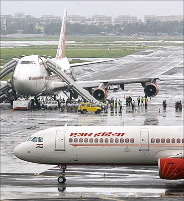 Air India's Boeing 747 aircraft (rear) stands on the tarmac after one of its engines caught fire.
