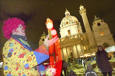 A clown juggles balls at a Christmas market in front of Karlskirche in Vienna.