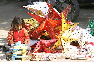 A girl selling Christmas decorations waits for customers in Ne