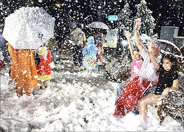 Tourists pose for photographs as soap suds simulating snow fall outside a mall in Singapore.