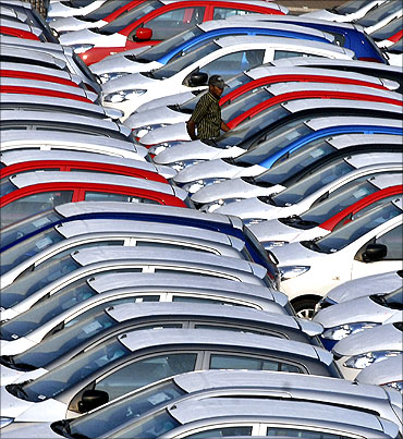 An employee checks parked Hyundai cars ready for shipment at a port in Chennai.