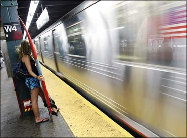 A woman holds her surfboard as the E line of the subway passes by the West 4th street station in New York.