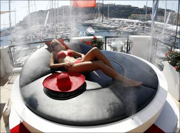 A model poses on a solar 'lazy sun bed' for luxury boats during the Monaco Yacht show.