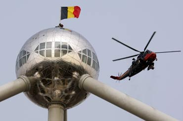 Belgian soldiers set up a Belgian flag on the top of Atomium in Brussels.