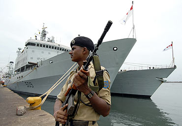 A security force personnel stands guard near the docked Canadian warships in Chennai Port
