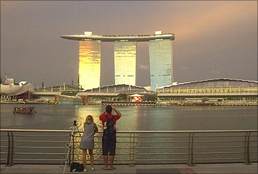 Tourists stand at a promenade across the water from the Marina Bay Sands.