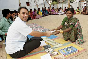 Akula giving money to a village woman.