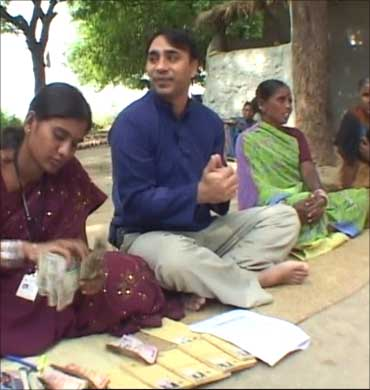 Akula disbursing loan to village women.