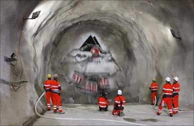 Miners watch as the ''gaby'' drill breaks through the rock at the construction site of the Gotthard Base Tunnel on June 16, 2009.