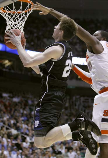 Gordon Hayward (L) goes up for a basket against Syracuse at a basketball game in Salt Lake City.