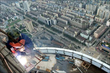 A Chinese welder works outside a building in downtown Chengdu.