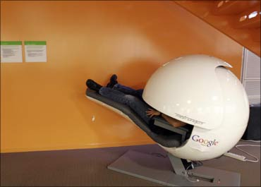 An employee takes a nap in a nap pod which blocks out light and sound at Google office.
