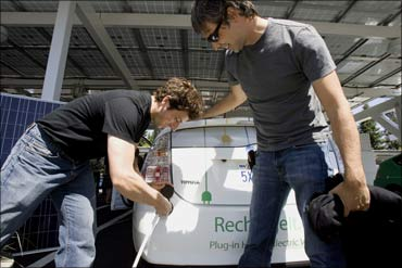 Google Inc. founders Sergey Brin  and Larry Page plug in an electric hybrid car at Google office.
