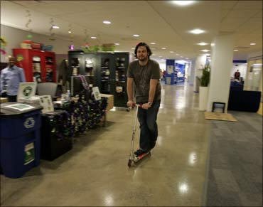 A Google employee rides a company scooter along the corridors at the New York City offices.
