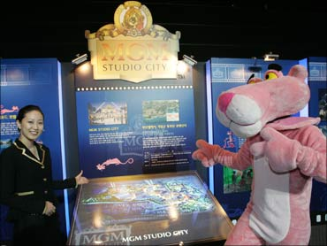 A South Korean woman poses with Pink Panther in front of a MGM theme park billboard in Pusan, Seoul.
