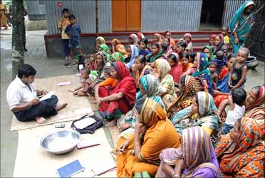 Women wait for a volunteer to distribute their loan money collected from a microfinance agency.