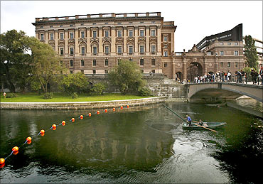 A fisherman lifts his net from a canal next to Sweden's Parliament Building, in Stockholm.