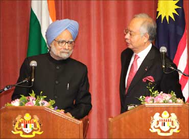 Prime Minister Manmohan Singh (L) listens to his Malaysian counterpart Najib Razak during their joint news conference at the latter's o