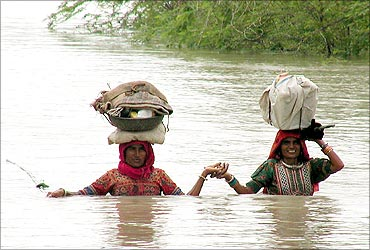 Villagers travel through heavy rain waters in the district of Kutch.
