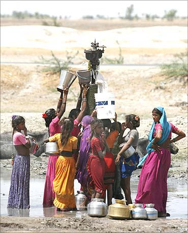 Women fill their buckets with drinking water that is leaking from a broken pipeline at Dharji.