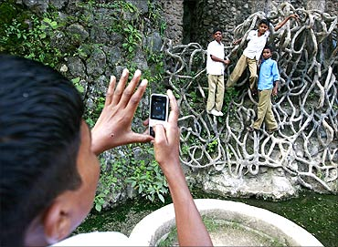 A schoolboy uses his cell phone to take a picture of classmates hanging onto cement roots.