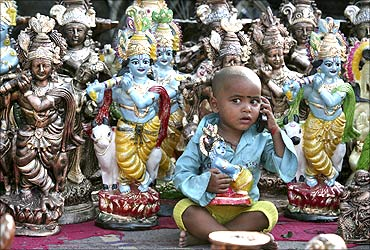 Prem (3), the son of an idol vendor, plays with a mobile phone.