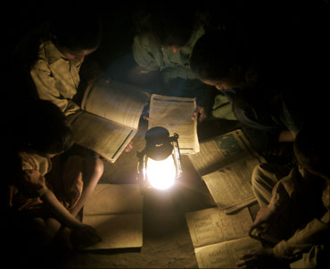 Children studying around a lamp due to power cut.
