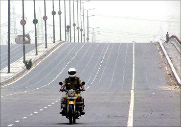 A policeman patrols a deserted national highway during a protest in New Delhi.