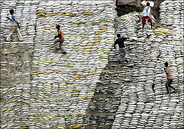 Labourers walk over the sacks of sand at the construction site of a commercial complex at Noida