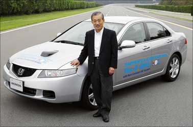 Honda CEO Takanobu Ito poses beside a diesel Accord.