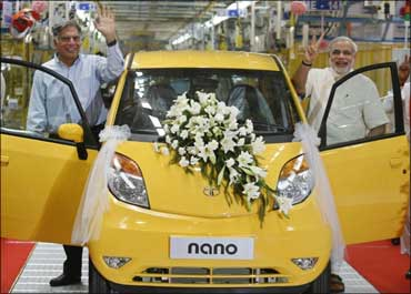 Ratan Tata (L), chairman of the Tata Group, and Gujarat's chief minister Narendra Modi wave as they stand beside the Tata Nano car during the inauguration ceremony of