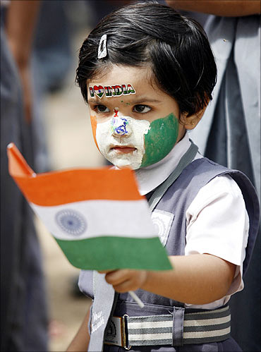A schoolgirl, with her face painted in colours of the Indian national flag.