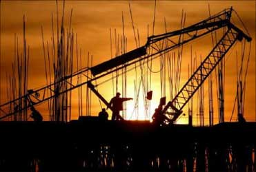 Construction workers work at a site as the sun sets in Chandigarh.