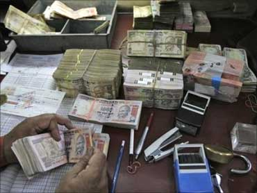 A bank staff counting Indian curremcy notes.